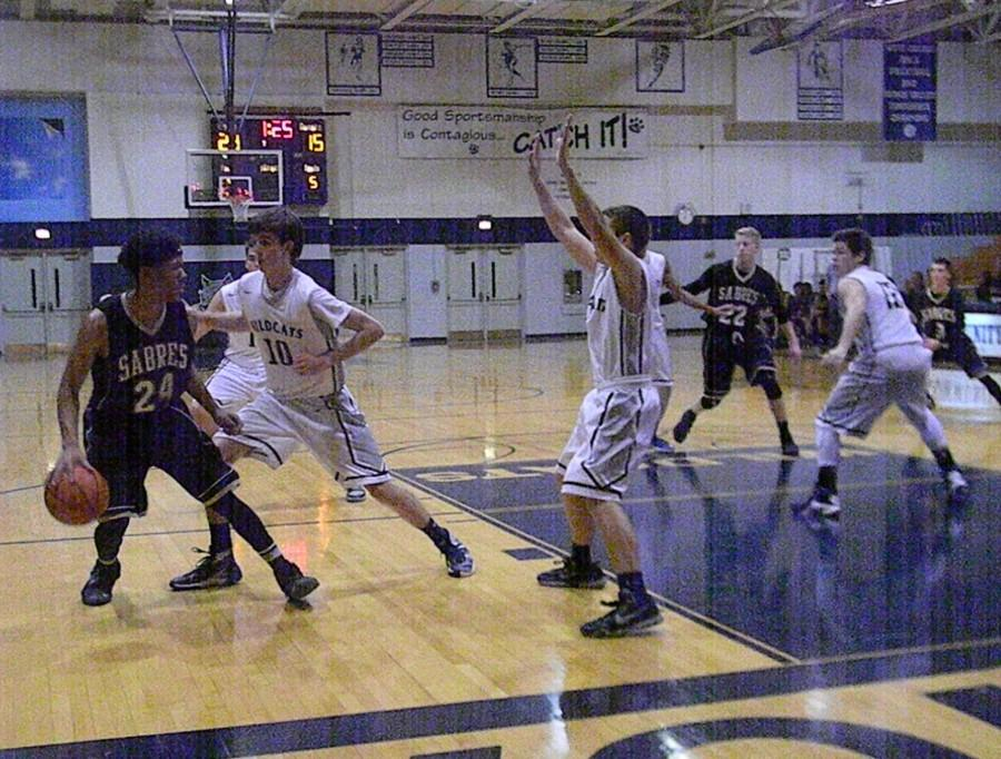 Streamwood High School struggled to score against the boys basketball team's defense. Senior guard Quinn Ricci and sophomore guard Jason Gimre defend against a Streamwood baseline drive.