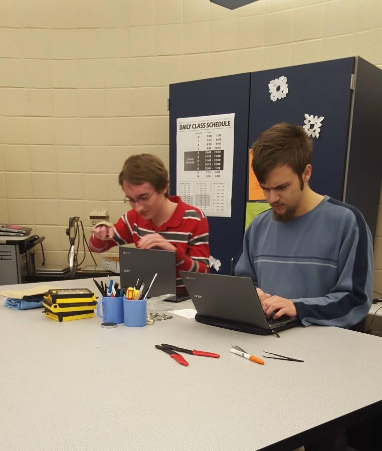 Using computers is a major factor in the job market, making TSI an important class. Senior Nathan Klapatch and junior Peter Delamater work on computers during TSI class.