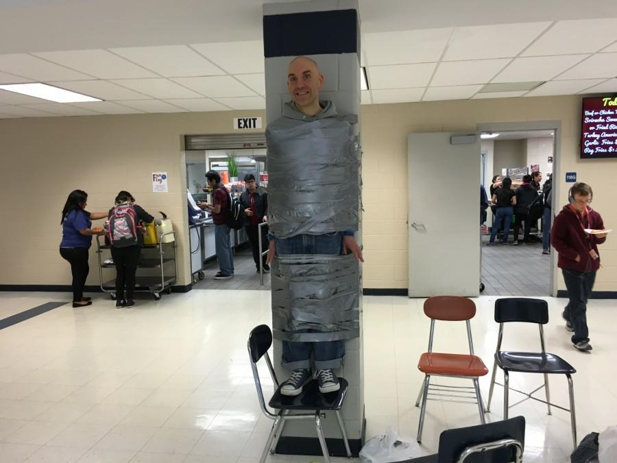 Drama Club adviser Mark Begovich allows students to duct tape him to a wall in commons during all lunch hours on March 22. as part of a fundraiser. The money raised will go towards an overseas trip to compete in the worlds largest performing arts festival.