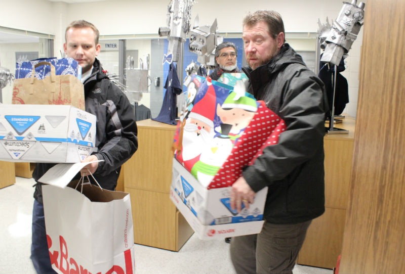 Staff donated Christmas presents to four Adopt A Family families. Assistant athletic director Bill Lech, right, and activities director Marc Wolfe are helping to deliver the presents to Adopt A Family.