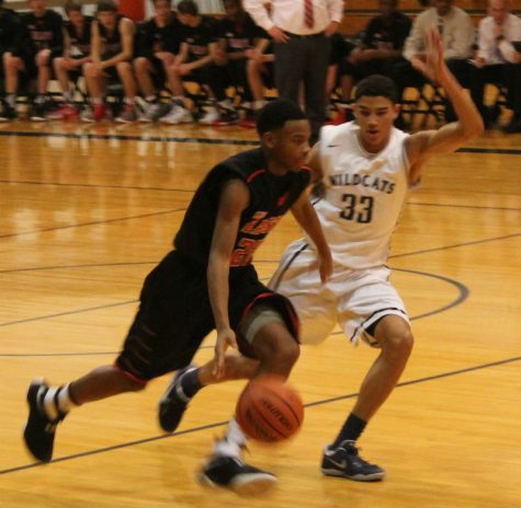 Senior Tai Bibbs blocks the basketball against Glenbard East. The team worked together to win the close game.