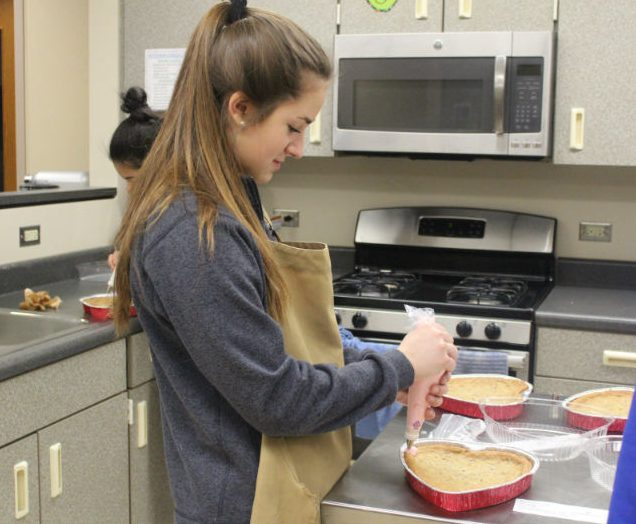 Foods 2 students decorate cookie cakes for customers who purchased them for Valentine's Day. Many clubs held fundraisers for the holiday.
