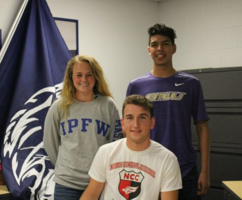 Seniors Emma Gaggioli (left), Sean Sweeney (middle), and Edgar Pani (right) signed to play soccer for their colleges. Parents stood next to the athletes as they signed for their commitment.