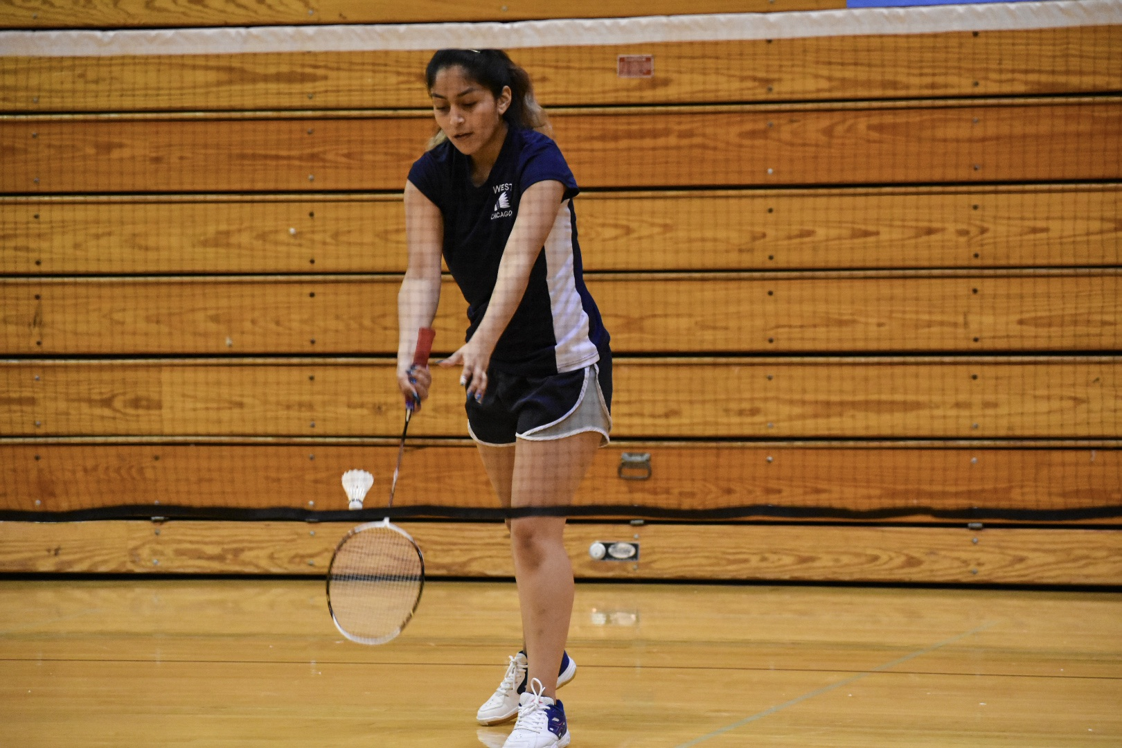 Senior captain Leslie Bueno serving in her singles match.