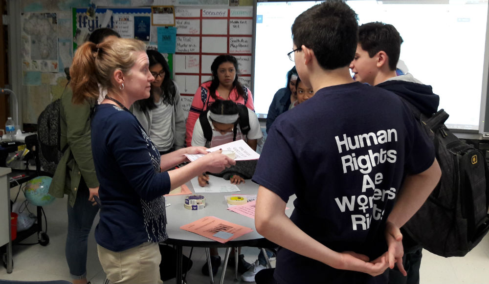 """WeGo Global adviser Maggie Haas instructs students as to where to place posters with human trafficking facts at Wednesday's meeting. WeGo Global hung up facts as part of their campaign """"We Won't Rest."""""""