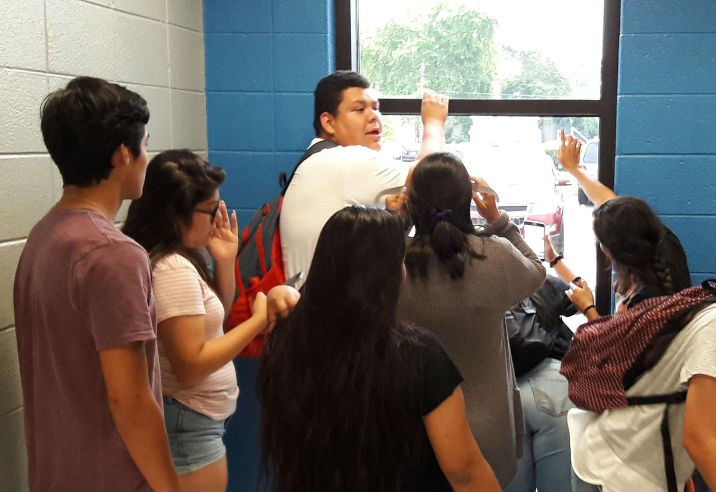 AP Spanish Literature students gather by the window to watch the eclipse.