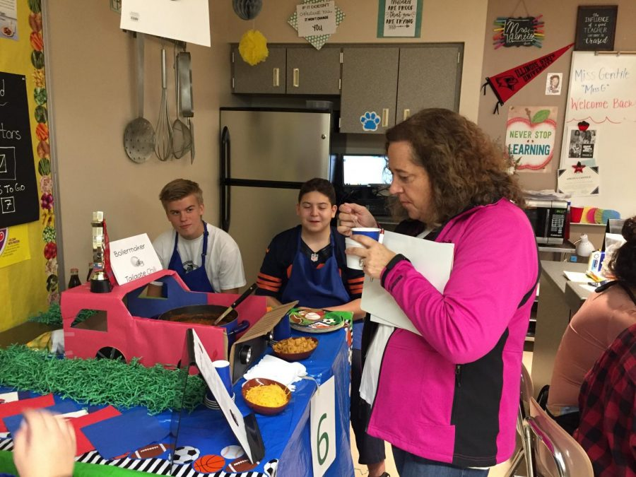 Staff members judged entries from the chili cook-off on Oct. 12. Special Education teacher Brigitte Debs tries tailgate themed dish that later won first place.