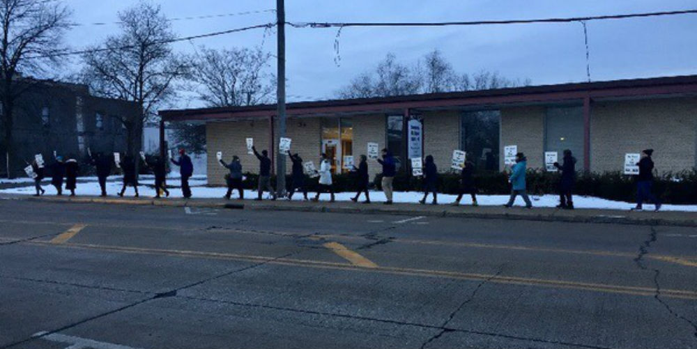 Teachers march and chant outside of the district office on Tuesday during a bargaining session.