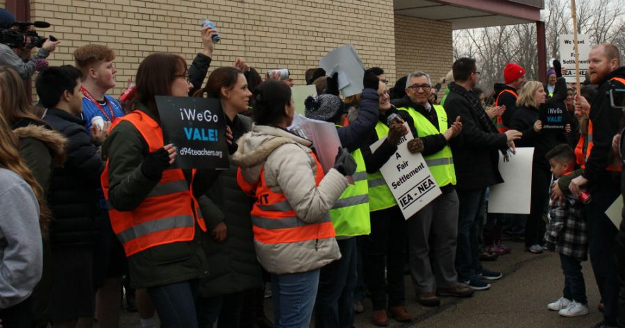 Association members, students, and community members cheer as the bargaining team enters the district office on Feb. 15.