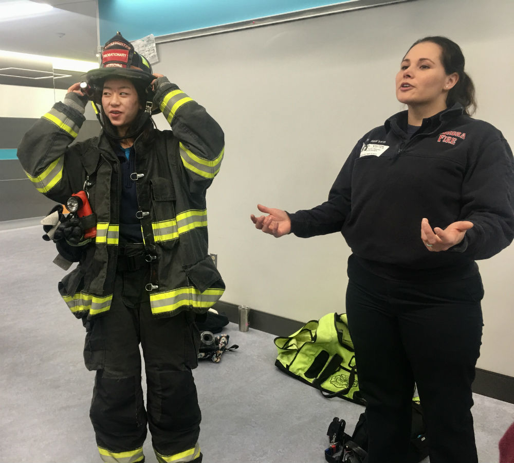 Sophomore Katie Sutherland tries on firefigther equipment brought by EMT paramedic Taylor Reeves for the HOSA panel event.