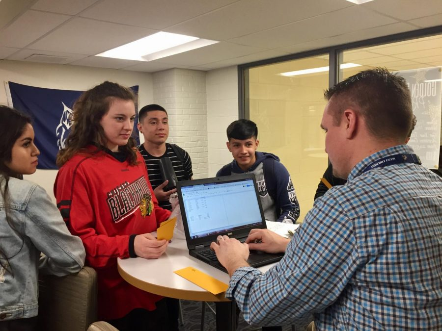 Student Council adviser Nick Kempski sells prom tickets to students during 10th hour in the student activity center.