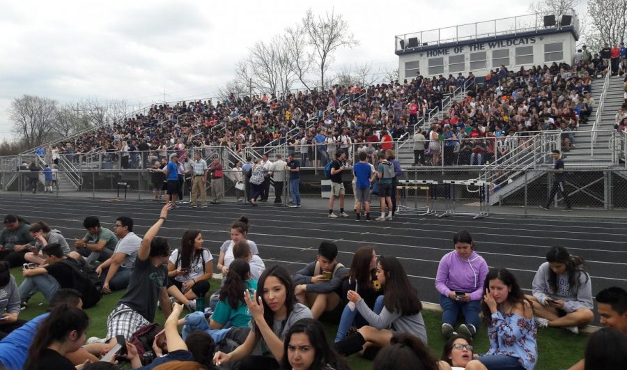 Students+waiting+on+the+football+field+and+bleachers+for+further+instructions+on+Wednesday.+