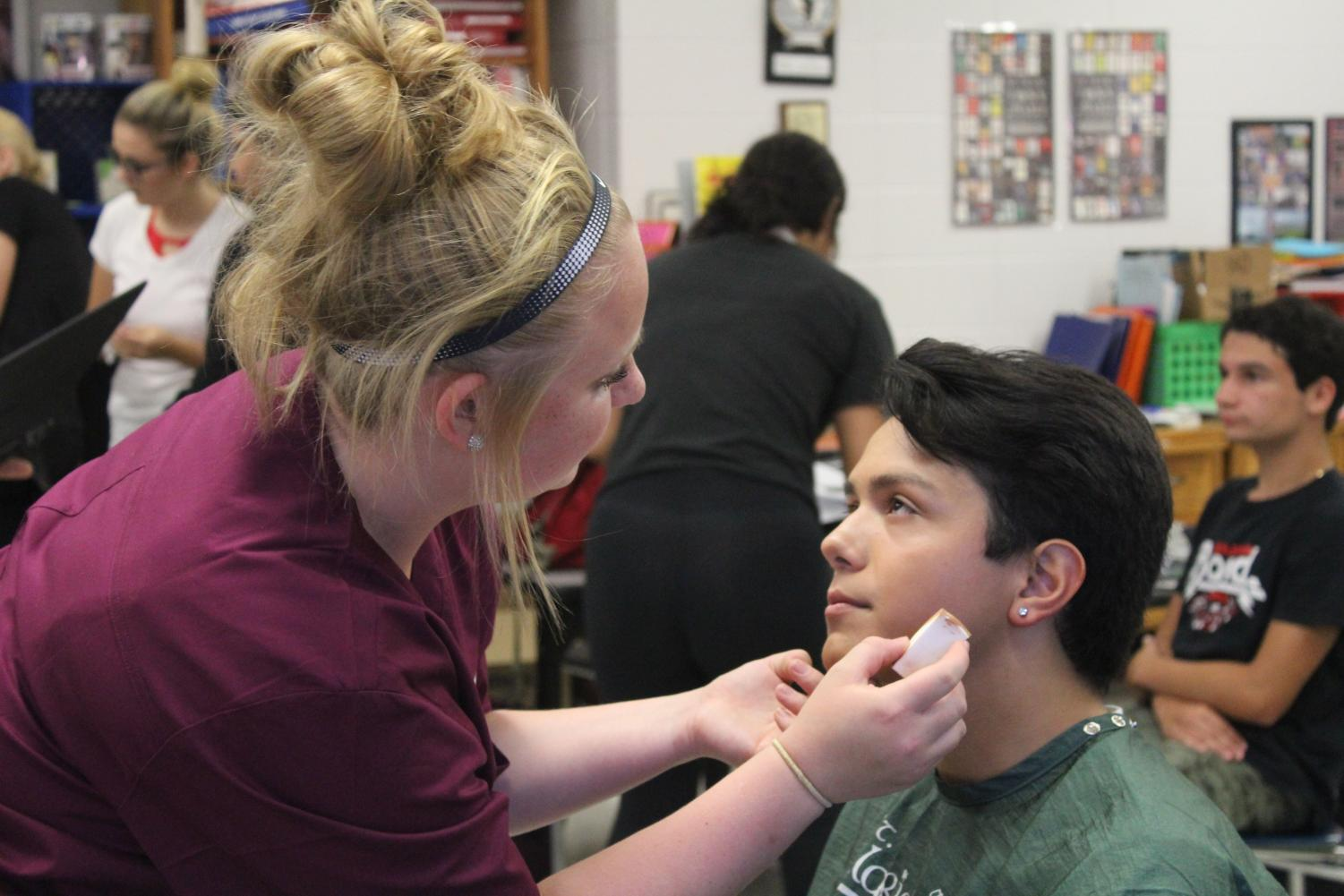 Makeup artist from the Technology Center of DuPage prepares senior Rudy Munoz for