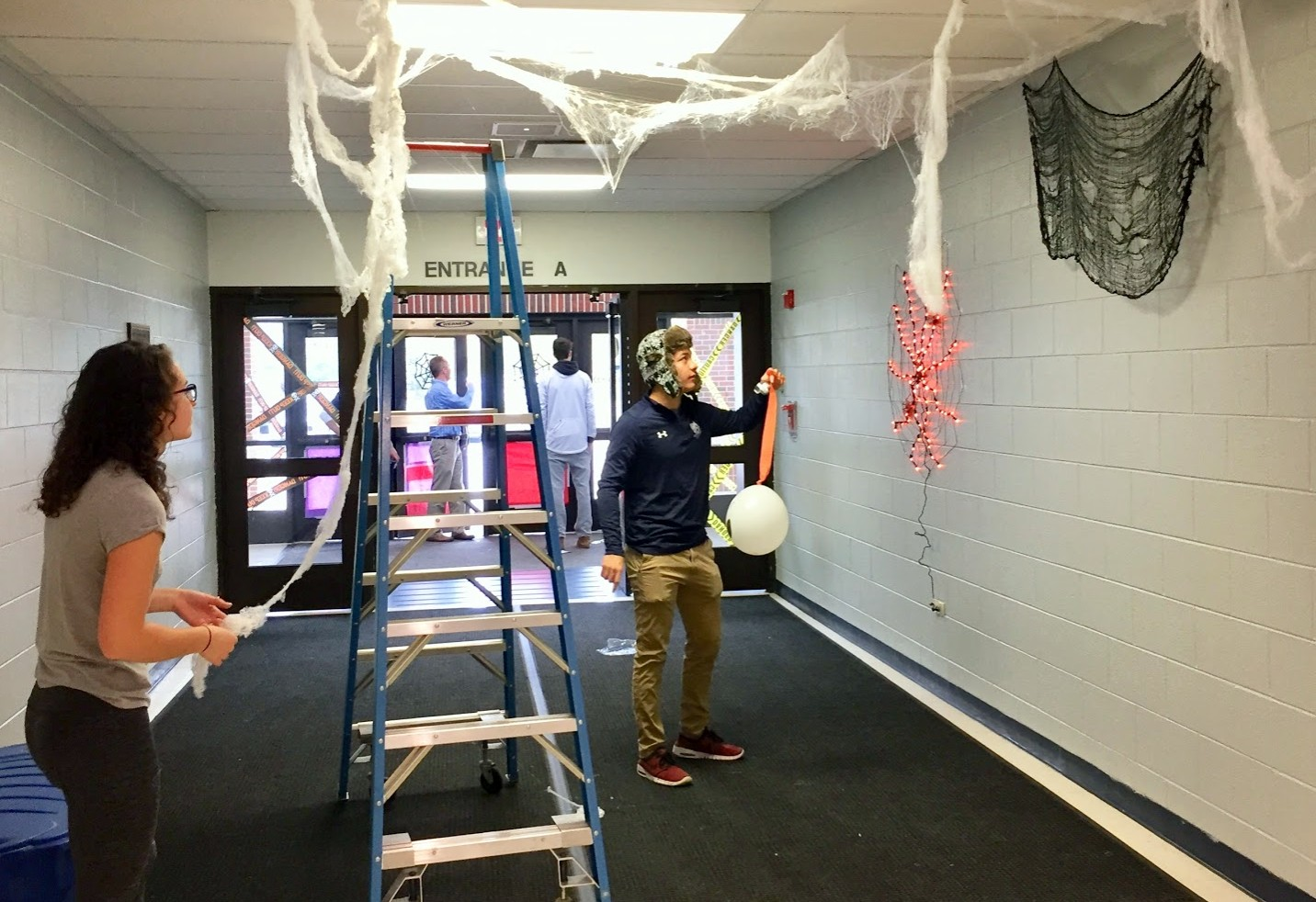 Student Council members, from left, senior Olivia Bartler and Adam Hey meet to decorate entrance A for Spooky Fest Friday.
