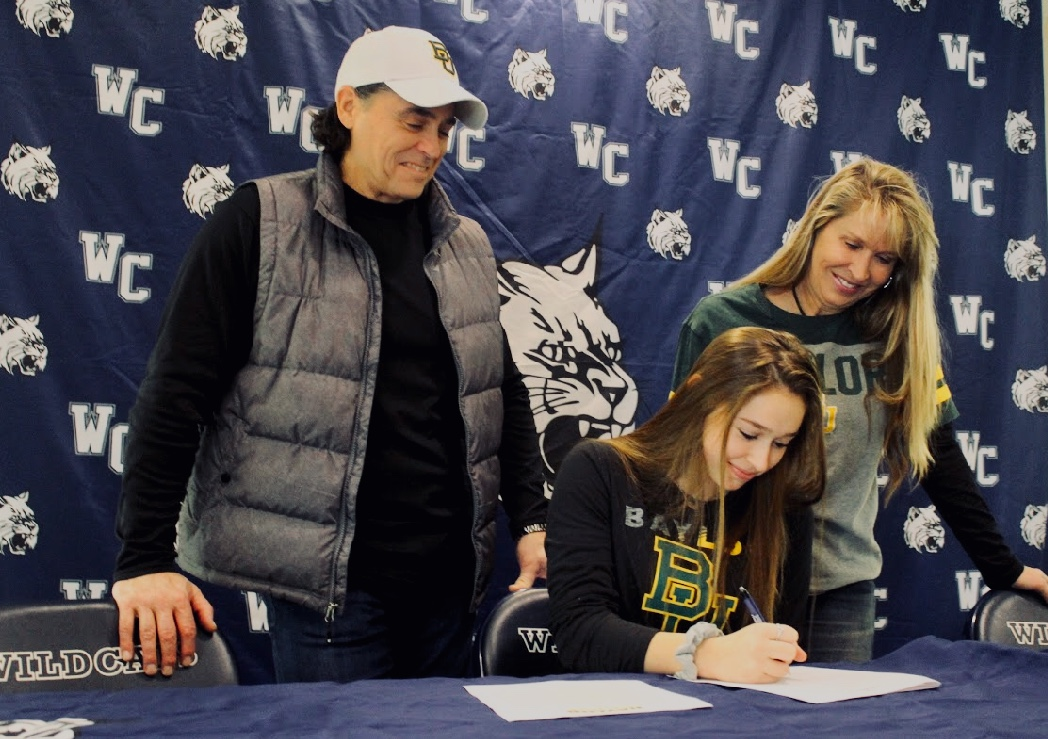 Senior Shaye Lauro signs a scholarship at Baylor University alongside her parents.