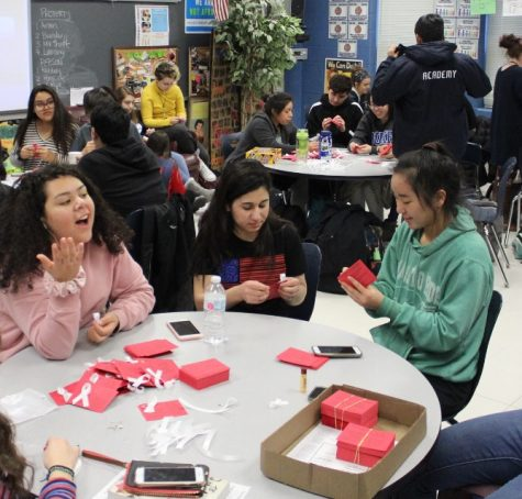 Information cards about the Yazidis will be distributed on Friday by WeGo Global members throughout the day. The white ribbon represents violence against women and support in spreading beliefs. From left, Sophomore Andrea Gutierrez, junior Ameena AlHammo, and sophomore Julia Nosky prepare the cards.