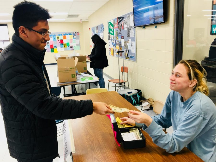 Sophomore Giovanni Benitez buys a ticket for the IHSA showcase during lunch from freshman Lizzy Ryan.
