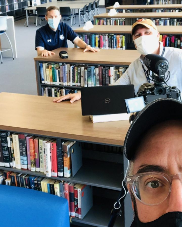 English teachers Dave Jennings (bottom right) and Brian Turnbaugh (middle right) prepare to interview Principal Will Dwyer for their video Cat Chat.